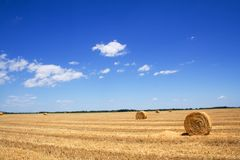 Stubble field and hay bales. Wide open stubble field with straw or hay bales under a spectacular summer sky Stock Image
