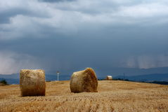 Stubble field and straw bales. Stubble field with straw bales after the harvest with a stormy sky royalty free stock photos