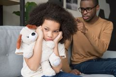 Stubborn african child girl closing ears ignoring angry black dad royalty free stock photography
