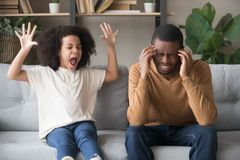 Stubborn african child girl in tantrum screaming at black father. Stubborn noisy african child girl in tantrum screaming at annoyed tired black father, naughty stock images