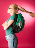 Stubborn, angry schoolgirl resisting to go to school. Stock Photos
