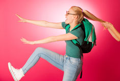 Stubborn, angry schoolgirl resisting to go to school. Wearing backpack and big eyeglasses, someone pulling her for two hair tails Stock Image