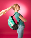 Stubborn, angry schoolgirl resisting to go to school. Stock Photography