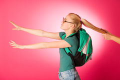 Stubborn, angry schoolgirl resisting to go to school. Royalty Free Stock Photos