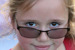Stubborn Beautiful Girl. A young blonde girl looking over the rim of her glasses in a stubborn but smiling look Stock Photography