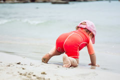 Stubborn child crawling towards water on beach during summer holidays. Stubborn baby crawling towards water on beach during summer holidays Stock Photography