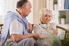 Stubborn elder wife. Old men is giving his stubborn elder wife medicine Stock Photos