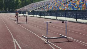 Stubborn girl spending days at stadium, training before hurdle race competition stock footage