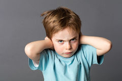 Stubborn kid with an attitude ignoring parents scolding, blocking ears Stock Photos
