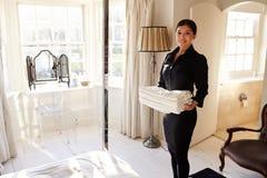 Stubenmädchen, das frisches Leinen in ein Hotelschlafzimmer trägt lizenzfreie stockbilder