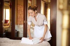 Stubenmädchen, das saubere Tücher auf Bett setzt Lizenzfreies Stockfoto