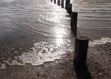Stubs моря деревянные при вода формируя и пенясь вокруг света солнца Стоковые Фотографии RF