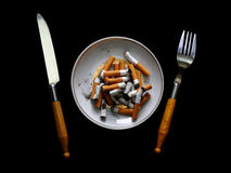 Stubs on a plate. Kitchen Knife, plug and plate with stubs on a black background stock images