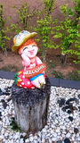 Stucco doll holding a welcome sign sitting on a timber Royalty Free Stock Photography