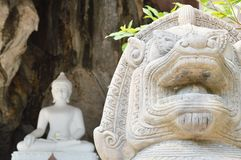 Stucco lion in front of white Buddha Stock Image