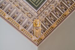 Stucco and luxurious decorative elements on ceiling. Luxury aesthetic in a home decor. Golden lion head pieces on a ceiling.  royalty free stock photography