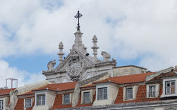 Stucco molding on the top part of a facade of the building against the sky with clouds to Lisbon, Portugal Royalty Free Stock Photo
