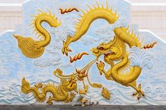 Two dragons fighting. Stucco sculpture of golden dragons fighting and shooting fire ball Royalty Free Stock Photo