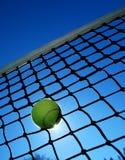 Stuck Ball. A Tennis ball stuck in a net backlit by the sun Stock Photos