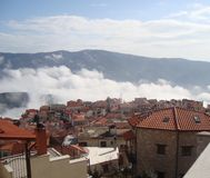 Stuck in a Cloud. A view of the Greek City of Arachova, Greece while a cloud is rising through the valley Stock Images