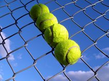 Stuck in a hole. Tenis balls in a metal fence Stock Photo