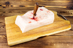 Stuck knife into the piece of fresh, raw pork lard on wooden board, rustic background. Stuck knife into the piece of fresh, raw pork lard on wooden board Stock Images