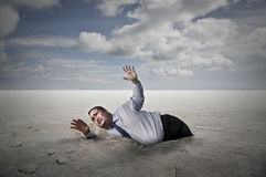 Stuck man. A man is stuck into the ground and asks for help royalty free stock image