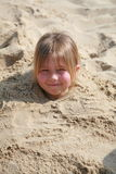 Stuck In The Sand. A young girl buried in the sand up to her neck Stock Photography