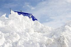 Stuck at the Top. Horizontal image of a shopping cart stuck at the top of a high snowbank Stock Image