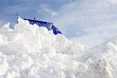 Stuck at the Top. Horizontal image of a shopping cart stuck at the top of a high snowbank stock image