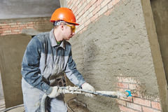 Stuckatör som besprutar murbruk på väggen royaltyfri bild