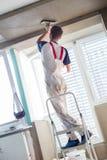 Stuckatör som renoverar inomhus väggar och tak Avslutande arbeten royaltyfri foto