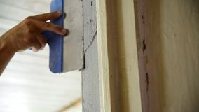 Stuckatören applicerar blandningen på dörrbrant sluttning stock video