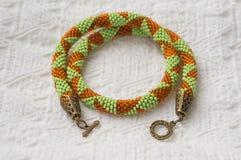 Stucken halsband från pärlor av ljus - gräsplan och orange färg royaltyfria foton