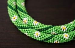 Stucken halsband från pärlor med bilden av blommor arkivfoton