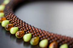 Stucken halsband från stora och små pärlor på en träyttersida royaltyfria foton