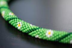 Stucken halsband med bilden av blommor på en grön bakgrund arkivfoto