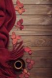 Stucken halsduk av burgundy färg med höstsidor och en kopp av Fotografering för Bildbyråer