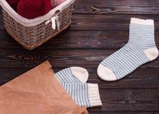 Stucken sockor och korg med garn på träbakgrund Royaltyfri Fotografi