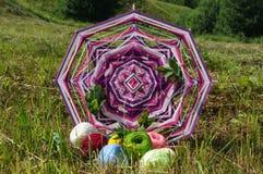 Stucken vävd mandala med garn på gräset Fotografering för Bildbyråer