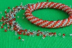 Stuckit armband från röda och gråa pärlor Royaltyfri Fotografi
