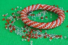 Stuckit armband från röda och gråa pärlor Arkivfoto
