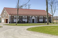 Stud farm of Bistrampolis manor ensemble at spring. Stone masonry, walls are decorated with red-bricks plastered surrounds. Built in XIX century. Neo-gothic stock photography