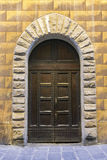Studded Timber Double Door. A strong wooden double door surrounded by a stone gothic archway in a stone block wall Stock Photos