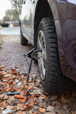 Studded tire wheel mounting on car with jack-screw at autumn Royalty Free Stock Photos