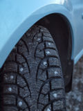 Studded tire on the winter road Stock Photo