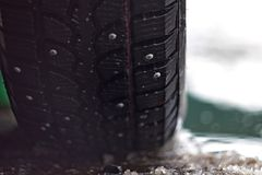 Studded tires in spring wet snow against the backdrop of water royalty free stock photos