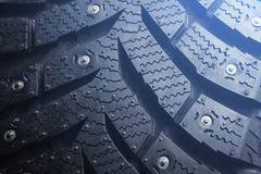 Studded winter tyre of the car. Toned glow.  stock photos