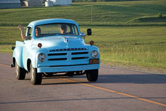 Studebaker Truck on a Country Road. This pickup truck was driving on a country road on a beautiful summer evening. It is painted light blue. The grass is green Stock Photos