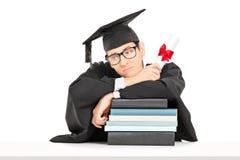 Studemt triste que sostiene el diploma y que se inclina en la pila de libros Fotos de archivo libres de regalías